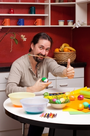 man with beard and Easter eggs holding up thumb photo