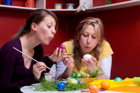 Two women tinker together and coloring eggs photo