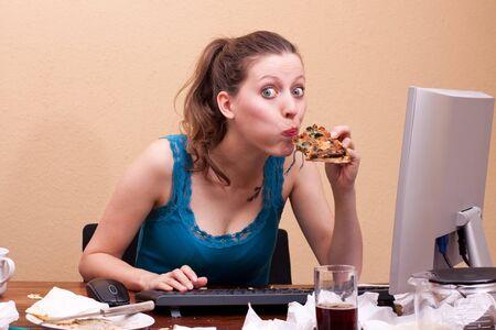 compulsive: pretty female secretary eats a piece of pizza