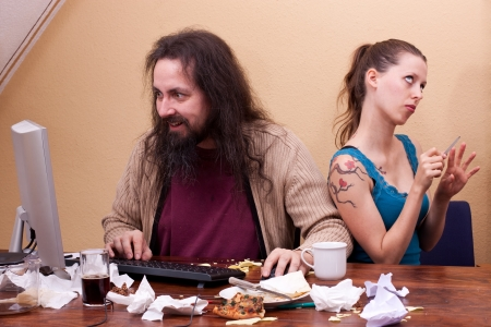 dirty girl: Long haired nerd on the computer with irritated beautiful woman Stock Photo