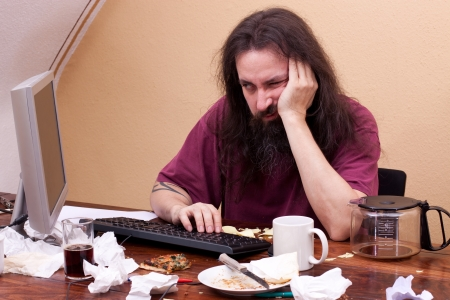 Frustrated man sitting on the pc and feels boring