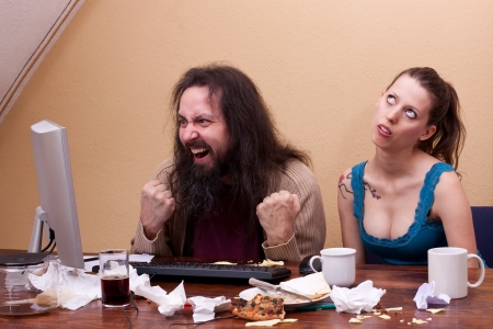 unkempt: Man celebrating success on pc, woman is rolling her eyes Stock Photo