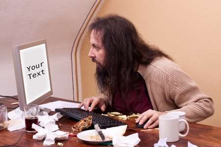 long haired nerd looks at monitor with space for text photo