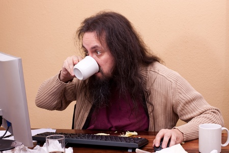 long haired man at dirty desk drinks a coffee photo