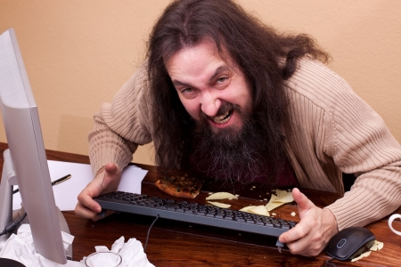 long haired: long haired angry nerd at a desk looking at viewer Stock Photo