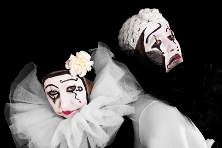 mimic: two sorrowful clowns with black background