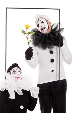 pierrot: two clowns in a frame with yellow flower Stock Photo