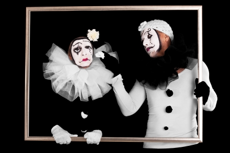couple of clowns in a frame, one looks sorrowful Stock Photo