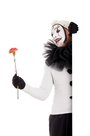 a male clown with a red flower in the hand photo