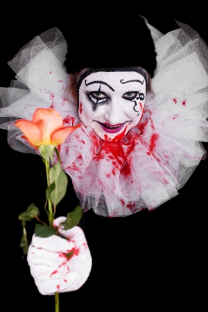 a creepy clown gives viewers a rose photo