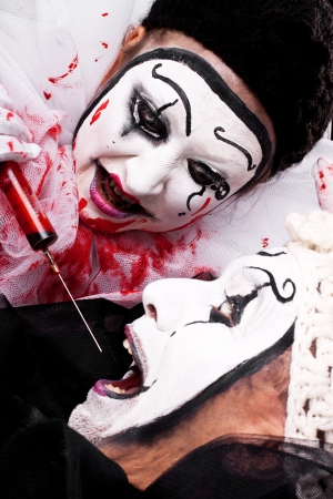 female evil Clown with syringe threatened male clown photo