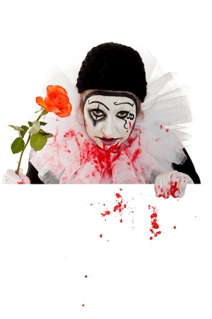 a fearsome female Clown with Rose looks over an edge photo