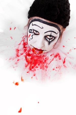 Fearsome female clown in front of white background with space for text photo