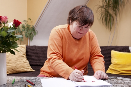 Disabled woman painted with colored pencils in a book