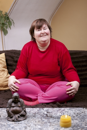constricted: mentaly disabled woman sitting cross-legged on the couch