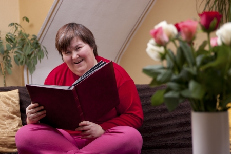 Mentally disabled woman is reading a book and smiles Stock Photo - 18866767