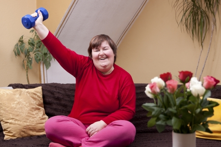 Mentally disabled woman shows her strength with a dumbbell Banque d'images