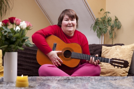 Mentally disabled woman playing guitar on a couch photo