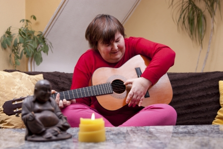 Disabled woman plays guitar and looks happy photo