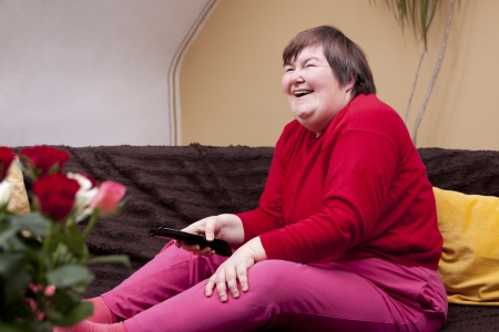 Mentally disabled woman watching television and laughs photo