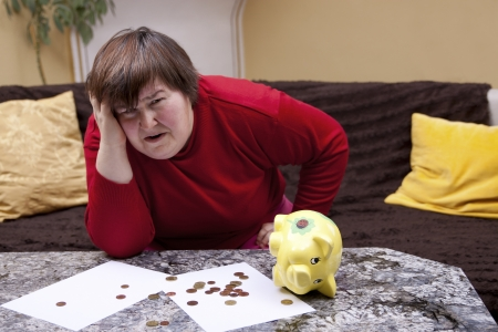 disability insurance: handicapped woman look desperate in front of her bills