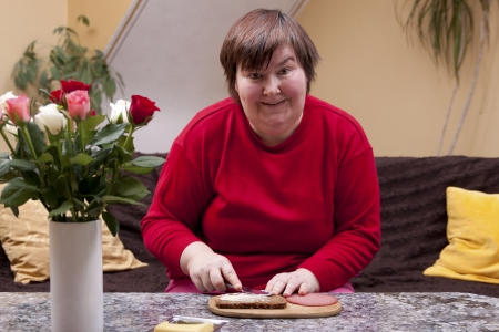defective: Mentally handicapped woman is making up a sandwich Stock Photo