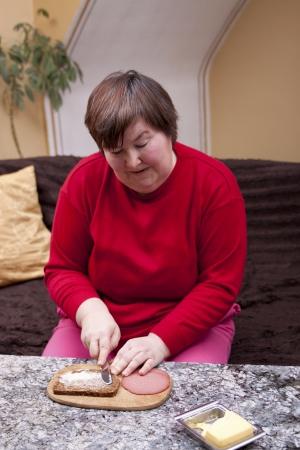 terapia ocupacional: mujer con discapacidad mental se hace un sándwich