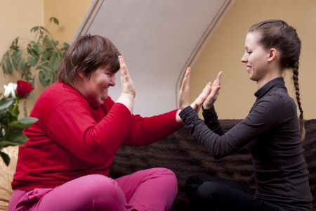 Two women, one of them disabled, making rhythm exercises Stock Photo