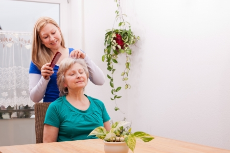 old carer: blond young woman combing seniors hair