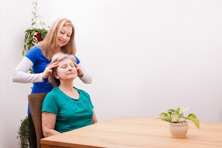 grandaughter: pretty Young woman massaging female seniors scalp