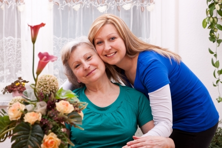 senior care: Mother and blond daughter in living room