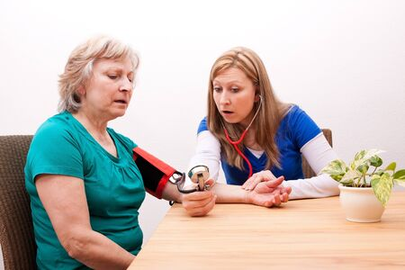female doctor measures senior adult the blood pressure photo