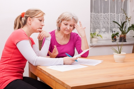 booking: Two women pondering in living room over documents Stock Photo