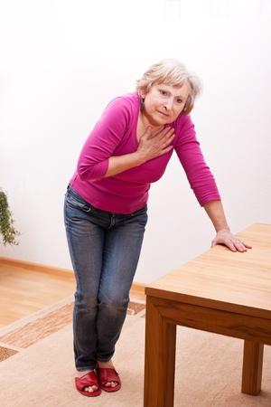 female senior has heart ache Banque d'images