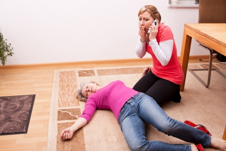 revitalization: female senior collapsed young woman calling help Stock Photo