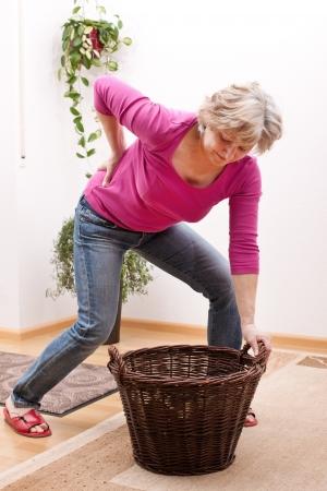 artritis: Hembra mayor con dolor de espalda debido a la pesada carga