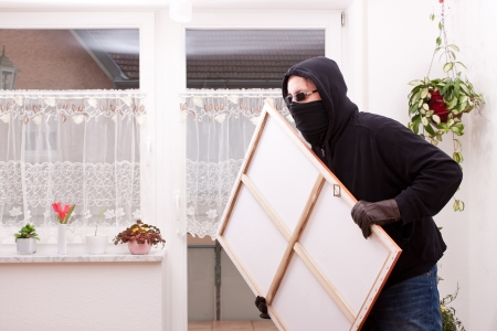 law breaker: masked Thief steals a painting Stock Photo