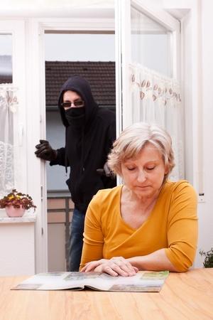 law breaker: burglar surprise unwary female senior Stock Photo