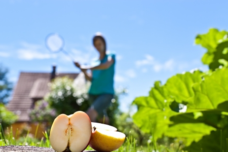 Young pretty woman with apple plays badminton photo