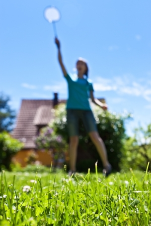 Young pretty playing badminton in the garden photo