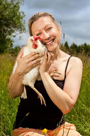 tierschutz: h�bsche blonde Frau umarmt eine wei�e Huhn