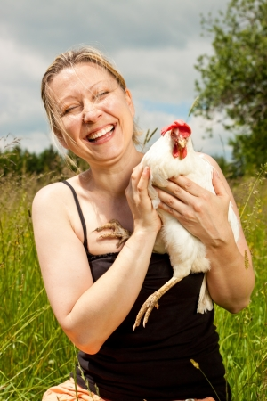 blonde beautiful woman hugs an cute chicken photo