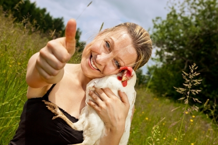 blonde woman with chicken lifts thumb up Stock Photo