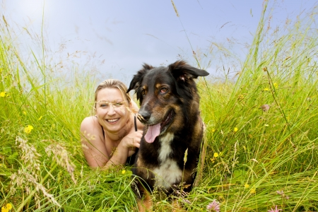 pretty woman with dog is lying on grass photo