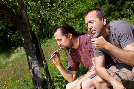 Two men relax with e-cigarettes
