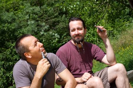 e cigarette: two men in nature with e-cigarette Stock Photo
