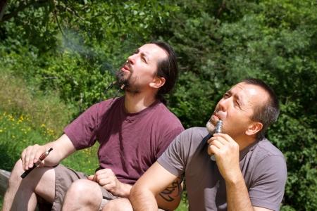 e cigarette: two men smoking e-cigarettes in nature