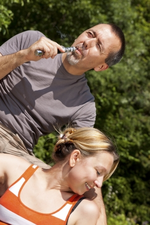 Couple relaxing with electronic cigarette photo