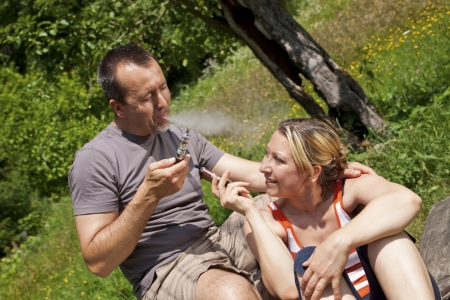 a Couple with e-cigarettes outdoor