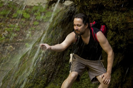 handsome hiker under a waterfall photo
